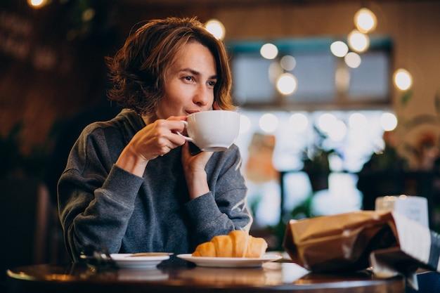 Joven mujer comiendo croissants en un café