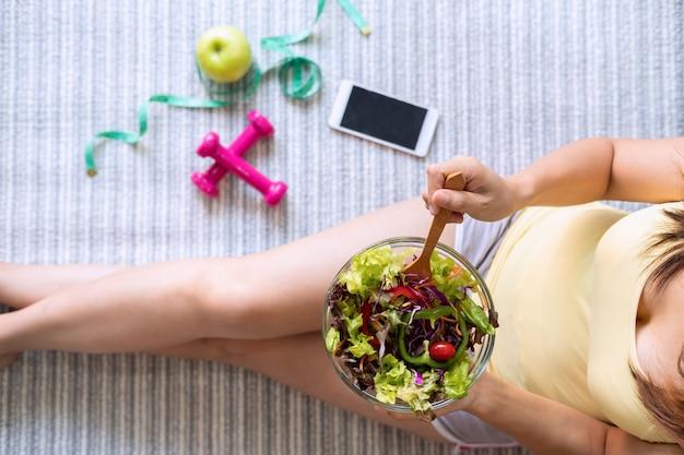 Joven mujer comiendo ensalada casera saludable en casa