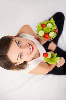 Joven mujer comiendo ensalada saludable después del ejercicio