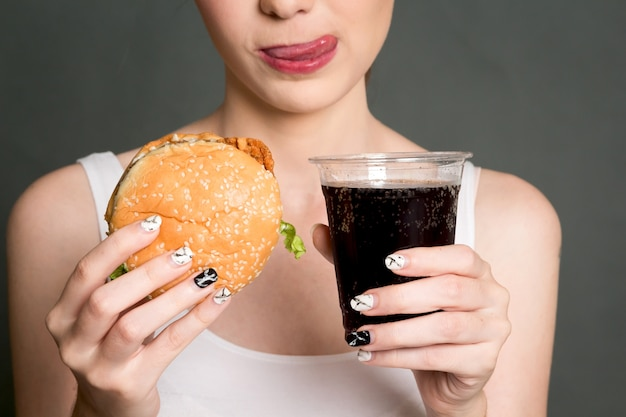 Joven mujer comiendo hamburguesas y cola sobre fondo gris