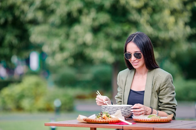 Joven mujer comiendo para llevar fideos en la calle