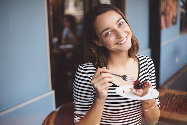 Joven mujer comiendo tarta de fresa