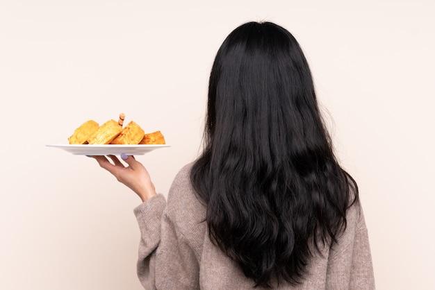 Joven mujer comiendo waffles sobre pared aislada