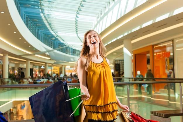 Joven mujer de compras en el centro comercial con bolsas
