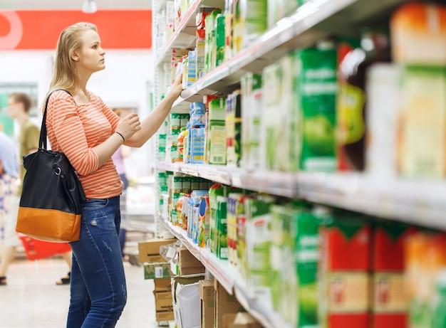 Joven mujer de compras de jugo en el supermercado