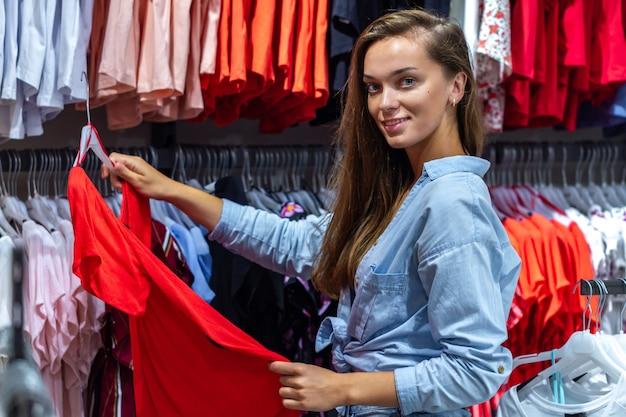 Joven mujer de compras en el mercado semanal de ropa