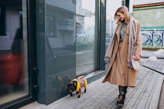 Joven mujer de compras con su perro bulldog francés