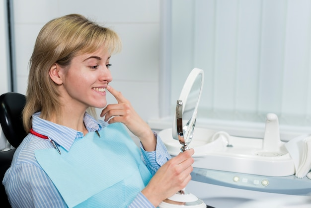 Joven mujer comprobando sus dientes en el espejo