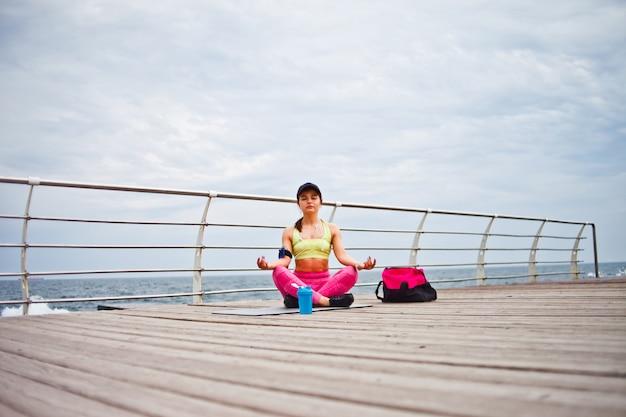 Joven mujer concentrada sentada sobre una estera de yoga en postura de loto en la playa