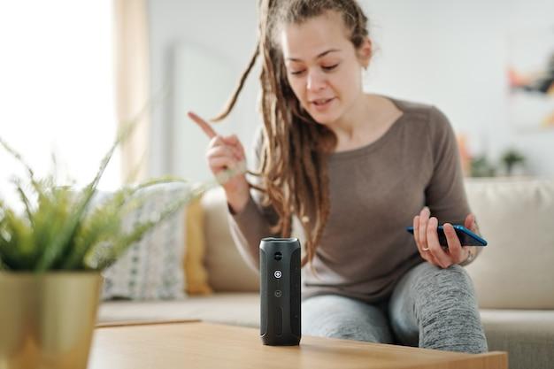Joven mujer contemporánea con teléfono inteligente sentado en el sofá frente al altavoz inteligente y haciendo preguntas