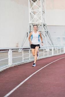 Joven mujer corriendo en el estadio
