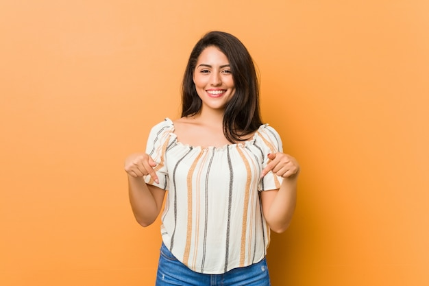 Joven mujer con curvas apunta hacia abajo con los dedos, sentimiento positivo.