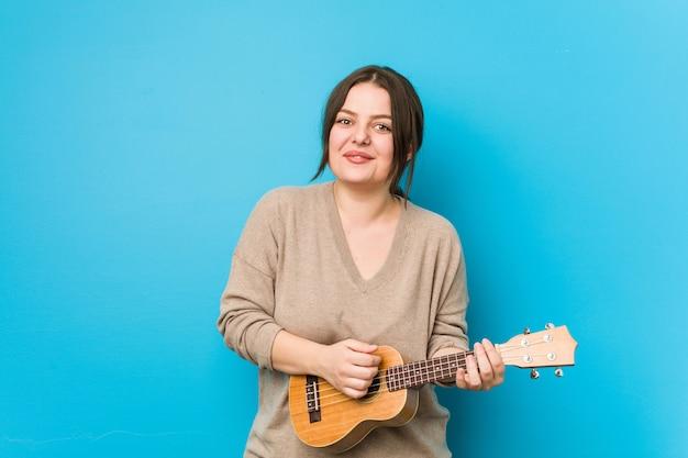 Joven mujer con curvas jugando ukelele aislado en una pared azul