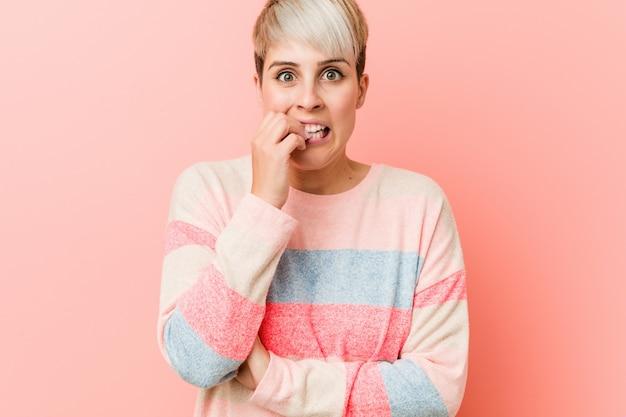 Joven mujer con curvas naturales morderse las uñas, nervioso y muy ansioso.