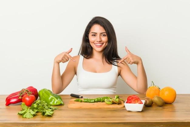 Joven mujer con curvas preparando una comida saludable apunta hacia abajo con los dedos, sentimiento positivo.