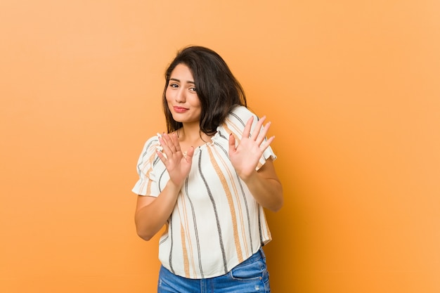 Joven mujer con curvas rechazando a alguien mostrando un gesto de disgusto.