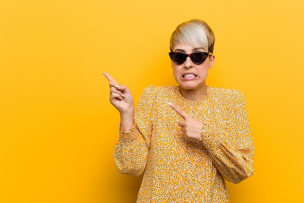 Joven mujer con curvas con una ropa de verano floral sorprendió señalando con los dedos índices a un espacio de copia.
