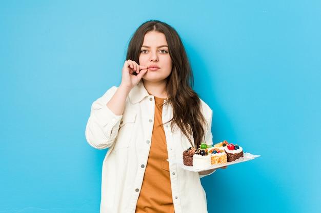 Joven mujer con curvas sosteniendo un dulce pasteles con los dedos en los labios manteniendo un secreto.