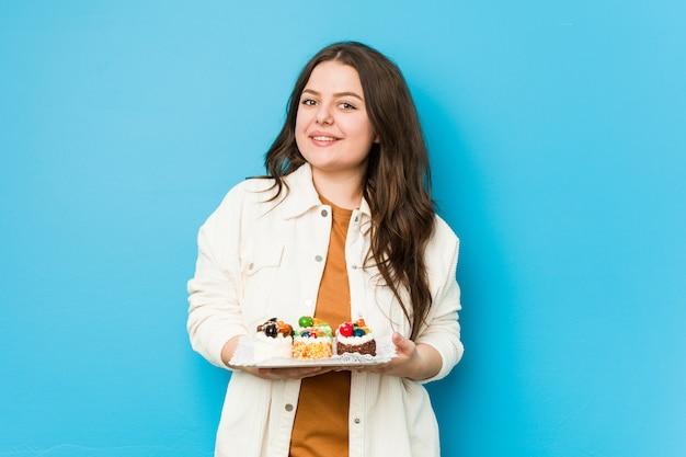 Joven mujer con curvas sosteniendo un dulce pasteles feliz, sonriente y alegre.