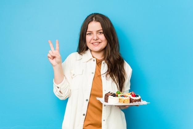 Joven mujer con curvas sosteniendo un dulce pasteles mostrando el número dos con los dedos.