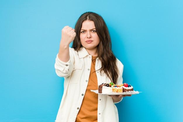 Joven mujer con curvas sosteniendo un dulce pasteles mostrando puño con agresiva expresión facial.
