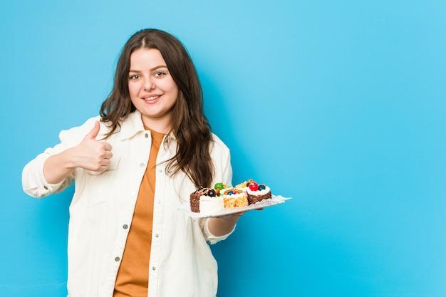 Joven mujer con curvas sosteniendo un dulce pasteles sonriendo y levantando el pulgar