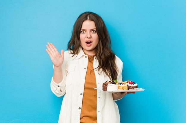 Joven mujer con curvas sosteniendo un dulce pasteles sorprendido y conmocionado.