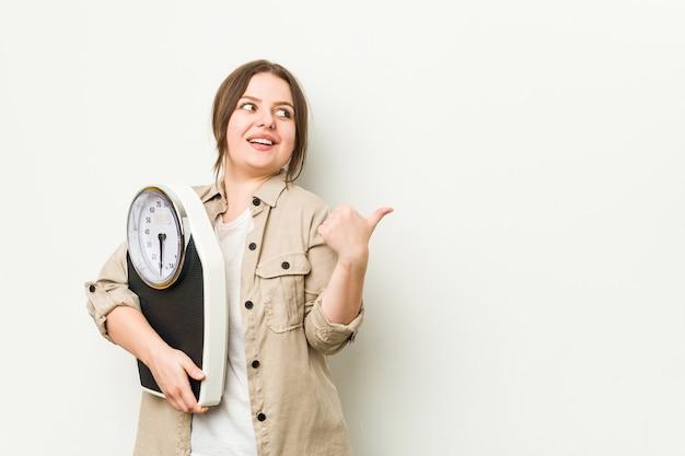 Joven mujer con curvas sosteniendo una escala apunta con el dedo pulgar, riendo y sin preocupaciones.