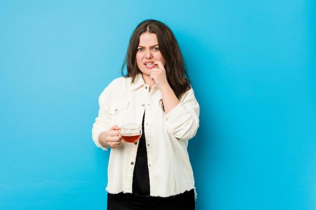 Joven mujer con curvas sosteniendo una taza de té mordiéndose las uñas, nerviosa y muy ansiosa.