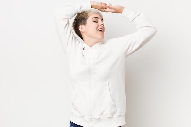 Joven mujer con curvas con una sudadera con capucha blanca estirando los brazos, posición relajada.