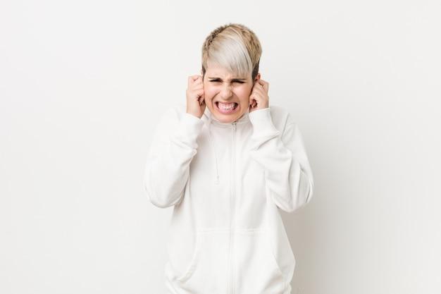 Joven mujer con curvas con una sudadera con capucha blanca que cubre las orejas con las manos.