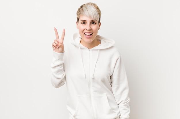Joven mujer con curvas con una sudadera con capucha blanca que muestra el signo de la victoria y sonriendo ampliamente.
