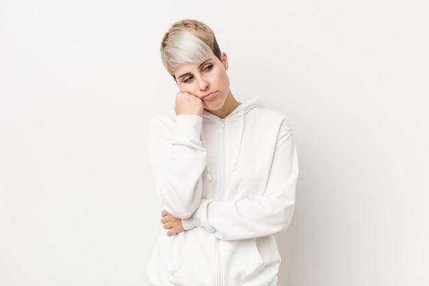 Joven mujer con curvas con una sudadera con capucha blanca que se siente triste y pensativa, mirando el espacio de la copia