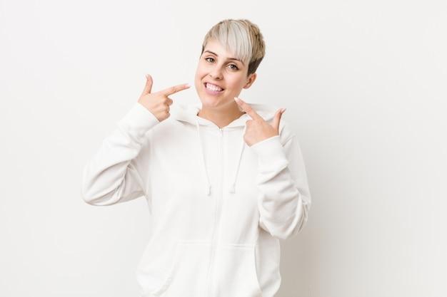 Joven mujer con curvas con una sudadera con capucha blanca sonríe, señalando con el dedo en la boca