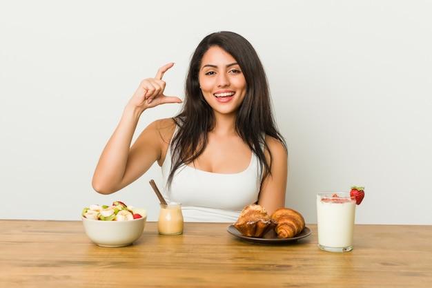 Joven mujer con curvas tomando un desayuno sosteniendo algo poco con los dedos índices, sonriente y confiado.