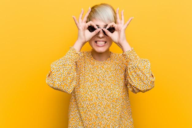 Joven mujer con curvas vistiendo una ropa floral de verano mostrando signo bien sobre los ojos