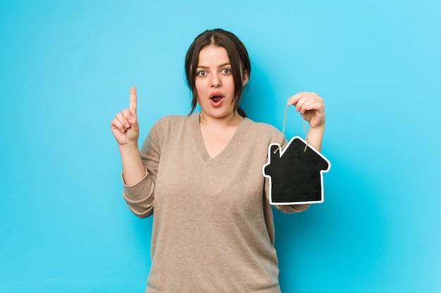 Joven mujer curvilínea de talla grande sosteniendo un icono de inicio con una gran idea, concepto de creatividad.