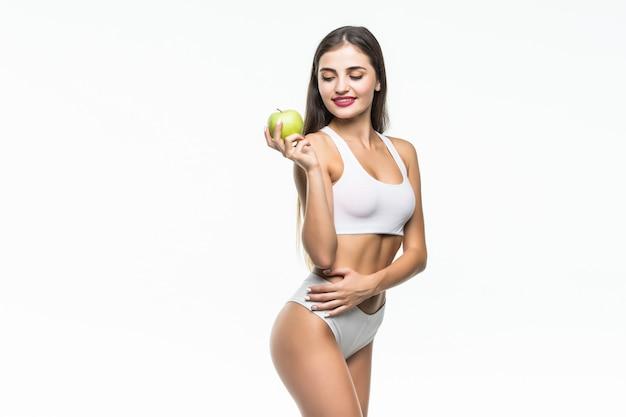 Joven mujer delgada con manzana verde. aislado en la pared blanca concepto de alimentación saludable y control del exceso de peso.