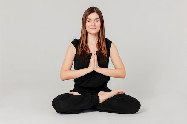 Joven mujer delgada morena en negro sentado en posición de loto