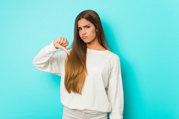 Joven mujer delgada mostrando un gesto de aversión, pulgares hacia abajo. concepto de desacuerdo
