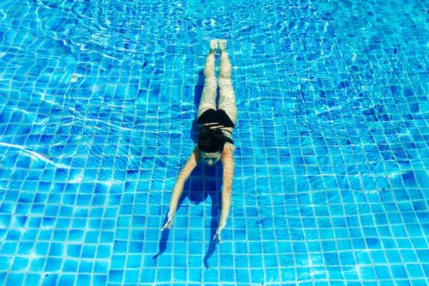 Joven mujer delgada relajante en la piscina con agua azul cristalina