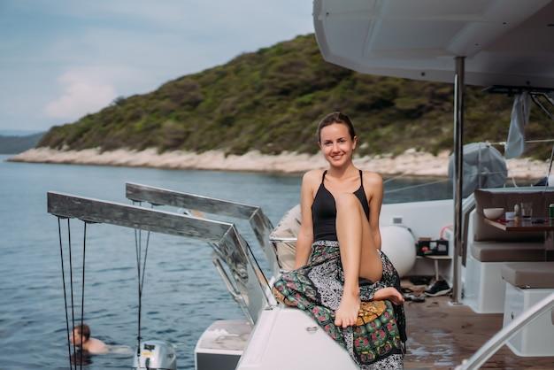 Joven mujer delgada sentada en traje de baño bikini en un yate y tomando el sol