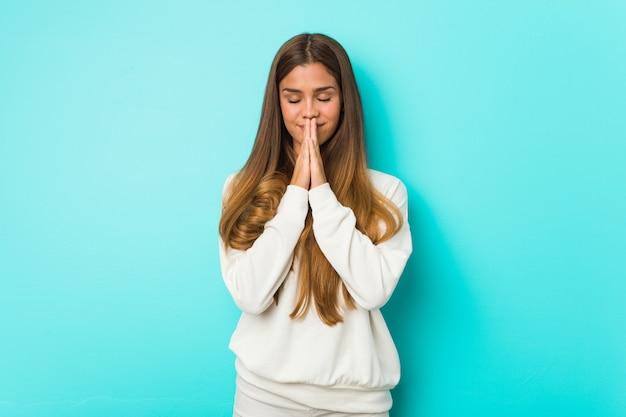 Joven mujer delgada tomados de la mano en rezar cerca de la boca, se siente confiado.