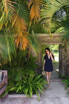 Joven mujer delgada en un vestido corto con un sombrero de paja en sus manos se encuentra a la sombra bajo palmeras tropicales en un hotel de lujo, bali, indonesia