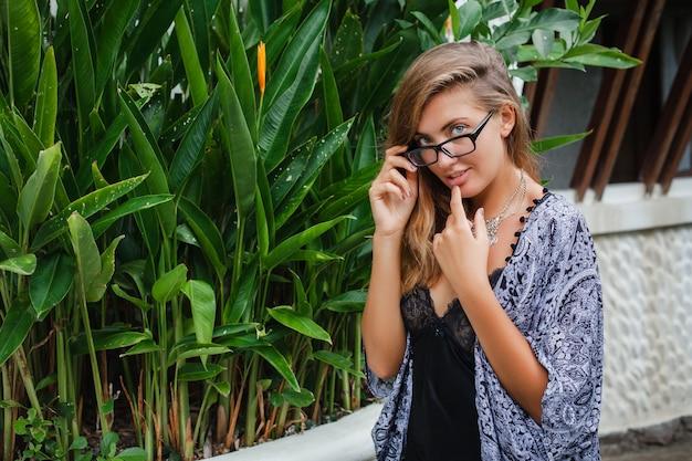 Joven mujer delgada en villa tropical de bali, con gafas y lencería