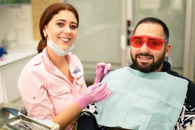 Joven mujer dentista médico y paciente sonriendo a la cámara en la clínica dental. gafas de seguridad para paciente. doctor en equipo de protección personal.