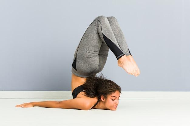 Joven mujer deportiva afroamericana haciendo poses de gimnasia rítmica