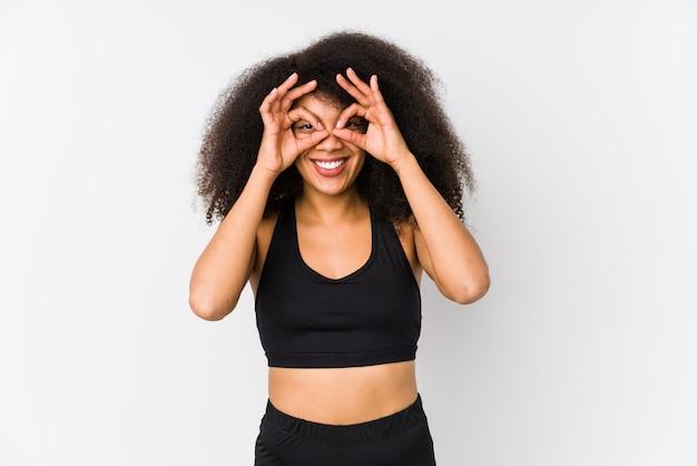 Joven mujer deportiva afroamericana mostrando bien firmar sobre ojos