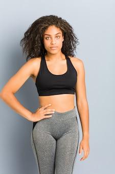Joven mujer deportiva afroamericana posando