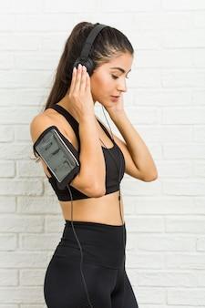 Joven mujer deportiva árabe escuchando música